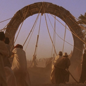 The front face of the stargate as it is lifted out of the pit it was buried in. Several symbols are visible, including the original symbol for Earth